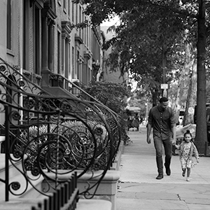 Man walking with child down city street